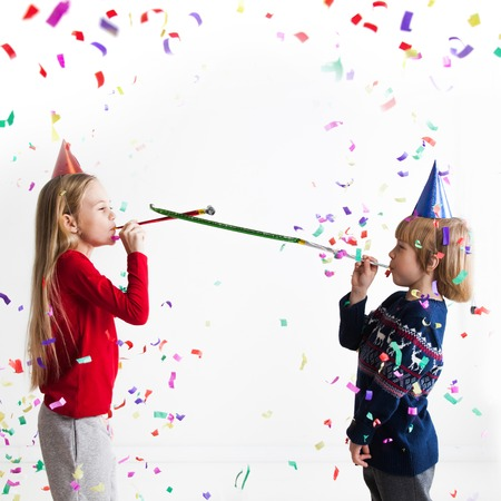 party popper: Children blowing party trumpets with confetti celebrating new year