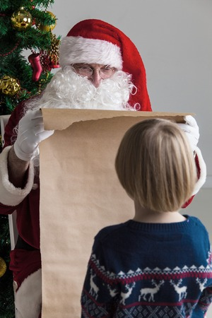 naughty or nice: Santa Claus holding list on old paper and child choosing gift Stock Photo