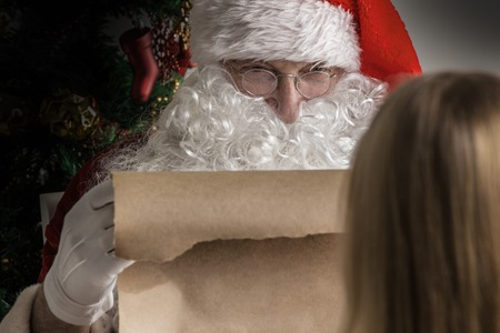 naughty or nice: Santa Claus holding list on old paper and girl choosing gift