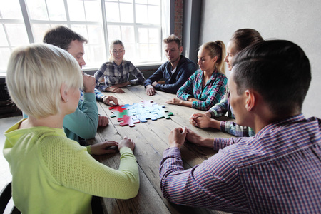 business puzzle: Business people and puzzle on wooden table, teamwork concept