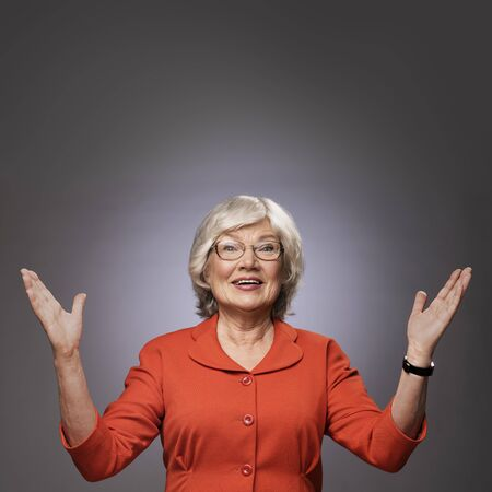 Happy senior lady with hands up on gray background with copy space. Finally! Thanks god! Thanks lord! Excitement concept.