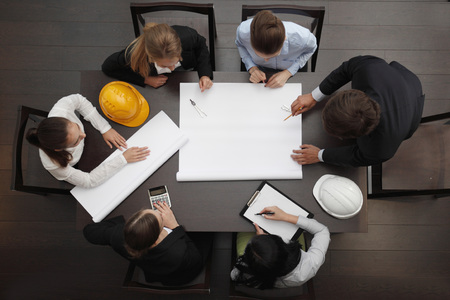 Top view of people around table in construction business meeting Archivio Fotografico