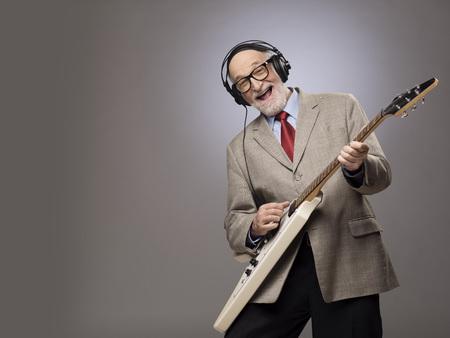 Happy funny senior man playing electric guitar Standard-Bild