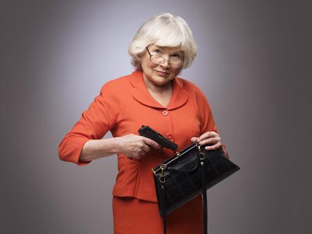 Senior woman putting a gun in her small handbag, self defence concept