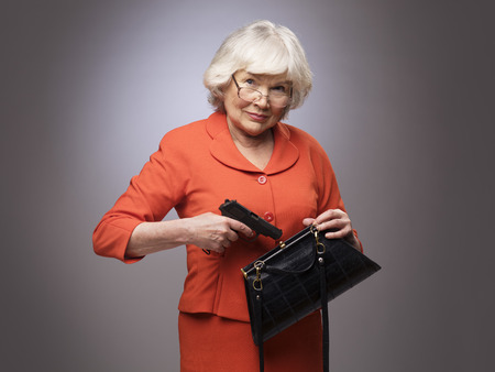 Senior woman putting a gun in her small handbag, self defence concept