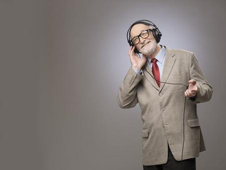 Portrait of senior man in headphones listening music, studio shot on gray background Stock Photo