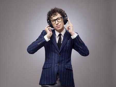 lyrical: Funny man in headphones listening music, studio shot on gray background