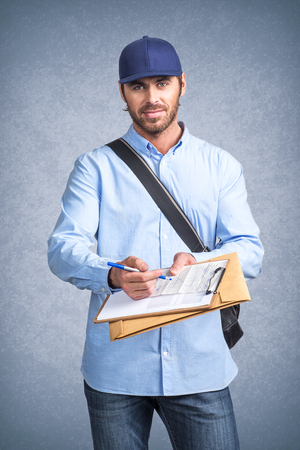 autograph: Handsome young delivery man holding document folder ask to sign invoice Stock Photo