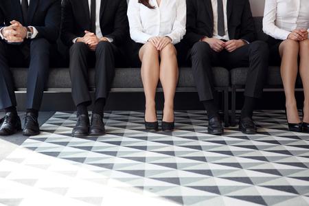 La gente que espera para la entrevista de trabajo sentado en las sillas en una fila
