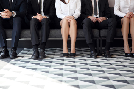 People waiting for job interview sitting on chairs in a row