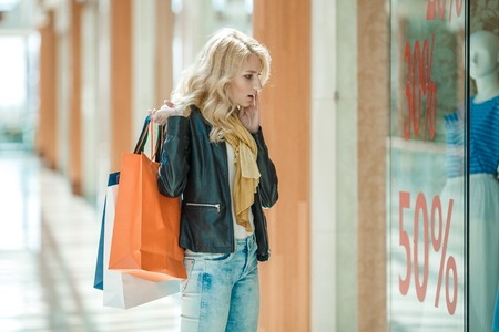 Beautiful young woman with mall bags looking shocked and surprised while shopping at sale