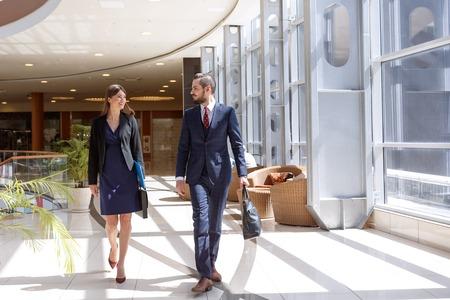 Socios de negocios hablando mientras camina en el centro de negocios