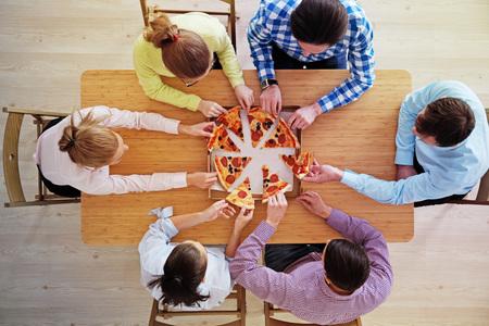Mensenhanden die pizza van leveringsdoos, hoogste mening grijpen Stockfoto