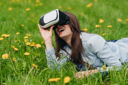 virtual reality simulator: Woman using the virtual reality headset outdoors laying in spring flower field