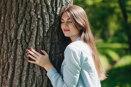 Young woman hugging a big tree, love nature concept