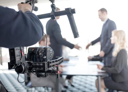 Videograaf die steadycam gebruikt, video van zakenmensen die handen schudden