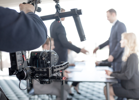 Videographer using steadycam, making video of business people shaking hands