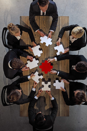 table top: Business people and puzzle on wooden table, teamwork concept