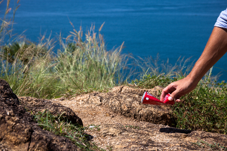 Man picking up litter can on rock at seaside