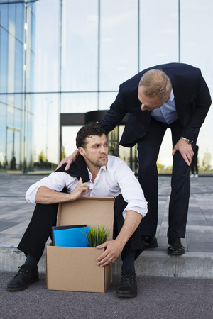 he: Fired business man sitting frustrated and upset on the street near office building with box of his belongings. He lost work. Other businessman comforts and encourages him