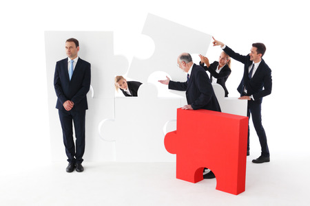 Business team assembling big puzzle and lazy businessman standing aside isolated on white background