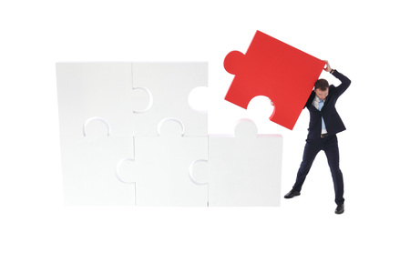Business pushing the final piece of puzzle isolated on white