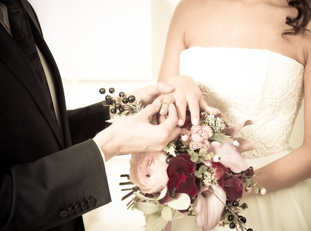 fingers put together: Groom places the wedding ring on the brides finger