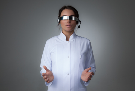 Female scientist or doctor using futuristic VR goggles headset with microphone and holding virtual object