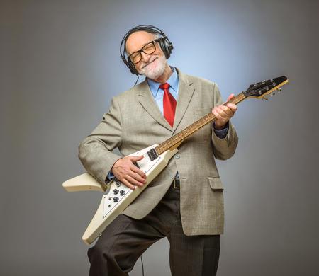 Szczęśliwy zabawny starszy mężczyzna gra na gitarze elektrycznej