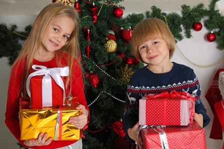 Portrait of two happy children with Christmas gift boxes and decorations. Two kids having fun at home
