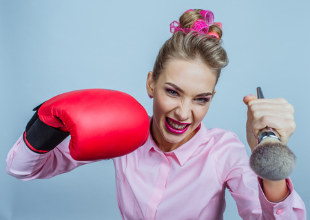 Fighting for beauty concept, funny woman with in boxing glove holding make-up brush