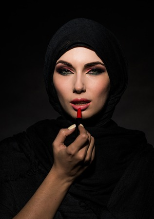 Young beautiful muslim woman putting red lipstick Archivio Fotografico