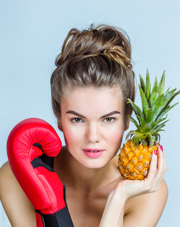 Young Woman with pineapple and boxing glove, fighting for healthy eating concept