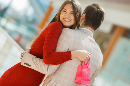 Happy beautiful young couple with gift bag hug in shopping mall Stock Photo
