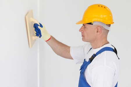 Builder working with grinding tool aligning wall indoors Stock Photo