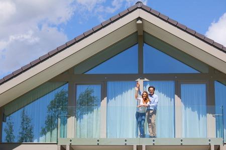 Heureux couple debout sur le balcon de leur maison et agitant les mains Banque d'images
