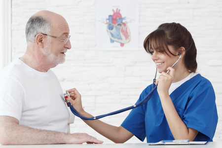 Doctor examining heartbeat of senior male patient