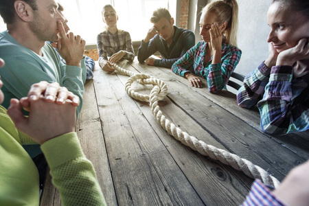 Problem solution concept, team of people in casual clothes sitting around the table with rope node Reklamní fotografie