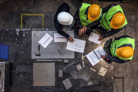 Workers and manager in safety helmets working with documents at factory