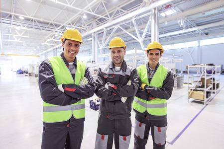 Team of three workers in uniform standing at background of CNC factory