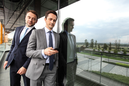 One business man spy on others businessman phone looking over the shoulder