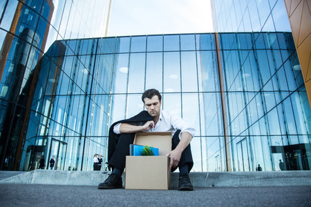 Fired business man sitting frustrated and upset on the street near office building with box of his belongings. He lost work Stok Fotoğraf