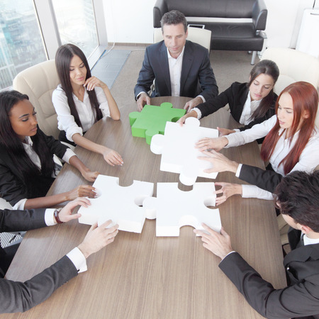 Group of business people assembling jigsaw puzzle and represent team support and help concept in office Stock fotó