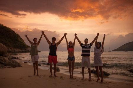 Group of happy people with raised hands at sea beach at sunset