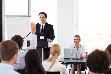 Group of speakers at business meeting at the table with microphones Stock Photo