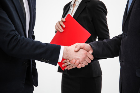 Business people shaking hands, finishing up a meeting, white background