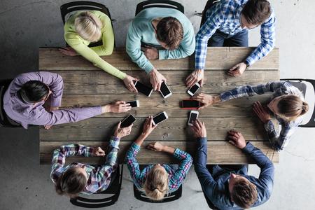 Equipo de personas pone teléfonos inteligentes a la mesa, concepto de comunicación en vivo Foto de archivo