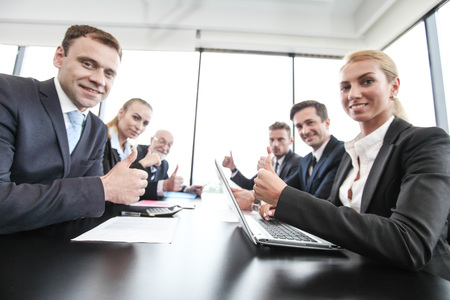 Mixed group of people in business meeting working with documents and computers showing thumbs up