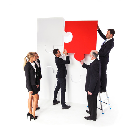 Business team assembling big puzzle isolated on white background