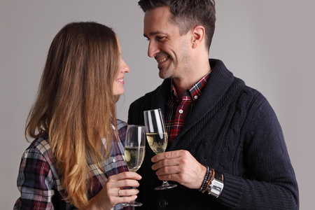 Happy mature couple in casual clothes embracing and clinking glasses of champagne Stock Photo